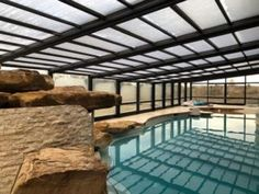 This residential retractable pool enclosure, manufactured by Roll-A-Cover, allows the homeowners to use their pool year-round, rain or shine. Swimming Pool Enclosures, Patio Enclosures, Swimming Pools, Outdoor Pool, Indoor Outdoor, Outdoor Ideas, Retractable Pool Cover, Solarium Room, Round Pool