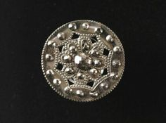 This flat steel button is pierced and set with polished faceted steels and decorated with 'mille grain', or tiny raised dots. There is a heavy half round steel shank.