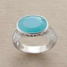 Fall under the sway of a faceted chalcedony stone, as infinitely blue and mysterious as the ocean. The stone is set in a scrollworked sterling bezel upon a sterling silver ring. Imported. Exclusive. Whole sizes 5 to 9.