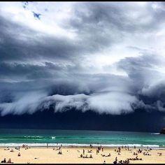 """Bondi Beach, bien aimée des surfeurs en Australie, a vu apparaître une drôle de vague le 6 novembre 2015. Celle-ci n'a pas débarqué de l'eau, mais du ciel ! Les gens sur la plage, muni de leur appareil photo, ont immortalisé un """"arcus"""", un nuage en rouleau."""