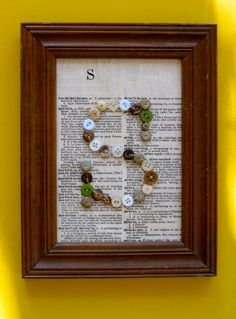 This is in an unpainted 5 x 7 wooden frame.    I used white, off white, brown and green wooden beads and buttons to create the S. The