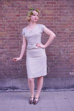 Prachtige jaren 50 vintage pencil dress met unieke halslijn en versierd met een strikje. Deze vintage jurk sluit met een metalen zij rits en met de bijpassende ceintuur accentueer je de taille!
