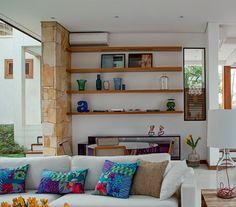 Perfeita para relaxar na companhia de amigos e da família, a sala de estar oferece conforto. Como no restante da casa, o ambiente conta com um ar-condicionado (do tipo split) cuja tubulação passa pelas paredes e pelo forro. No teto, o rebaixo de gesso embute as luminárias e um sistema de áudio e vídeo. Almofadas de malha da Interiores Confecções, abajur da Bertolucci e pufe de Ana Morelli