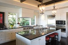 50 Dream Kitchens You Desperately Want To Cook In - Porch.com Windows behind cooktop. Lantern light fixtures are simple, yet elegant