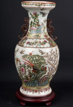 Description A Chinese porcelain 'famille rose' style two handled baluster vase brightly decorated in many colours with large exotic & smaller birds perched among boughs in a rocky garden planted with bamboo & flowering prunus, & with moths flying within horizontal reserved bands, the base with a iron red printed mark of the Qianlong emperor (1736-1795) within a square  Date 20th century.  www.collectorstrade.de