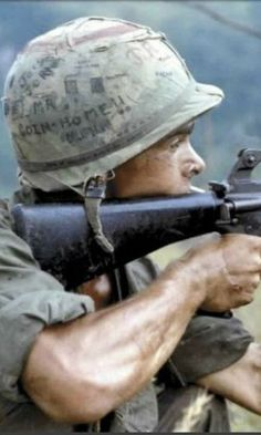 PFC Michael J.) fires is rifle into a suspected Viet Cong occupied area. PFC Mendoza was a rifleman with A Company Battalion Infantry Airborne Brigade.