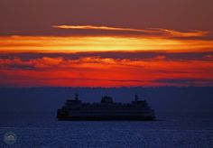 The sun sets in Seattle over an iconic Washington State Ferry
