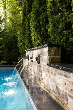 Swimming Pool Fountain Ideas raised planting area with waterfall really cool stuff pool ideaspatio Fountains Into Pool Stone Wall Evergreens