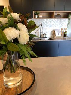 Matt black kitchen with timber shelf detailing, Caesarstone sleek concrete benchtops and herringbone marble-look splash back tiles.
