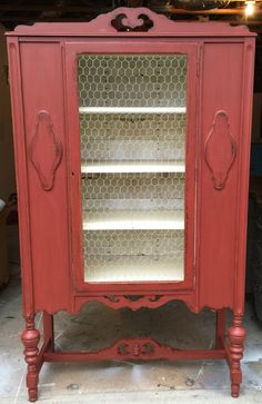 New Old Finds custom mixed brick red and buttercream icing! Distressed, chicken wire and white washed decoupaged paper just add that awesome element of farmhouse to this lovely antique china cabinet!