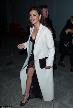 Wrapped up: Penelope opted for a far more demure style on her way into the event however as she banished the evening chill beneath a white trench coat which conceded just inches above the floor