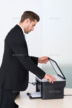 Buy Businessman Using Photocopy Machine In Office by AndreyPopov on PhotoDune. Side view of young businessman using photocopy machine in office Wireless Printer, Side View, Stock Photos