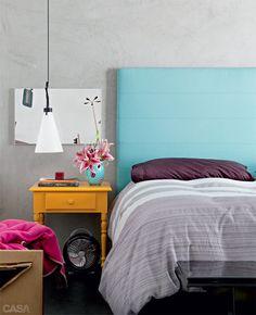 Cabeceira na moda. O azul-tiffany, em alta na decoração, cobre o painel estofado de 2 x 1,50 m. Para contrastar, o criado-mudo ficou amarelo-gema. Roupa de cama da Calvin Klein.