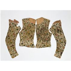 These pieces once formed part of a woman's jacket and are beautiful examples of the splendour of British embroidery between 1600 and 1620. The foundation pattern in plaited braid stitch with silver-gilt thread is strapwork, a design also used in other decorative arts of this period. The leaves and flowers are filled in with a detached buttonhole stitch in a variety of coloured silks. The grapes have been worked over thick padding to give them an almost three-dimensional shape.