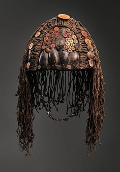 Lega artist Place made: Democratic Republic of the Congo Hat, 20th century Fiber, mussel and cowrie shells, and buttons h. 38.1 cm., w. 25.4 cm., d. 22.9 cm.