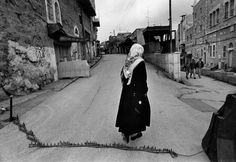 Larry Towell  ISRAEL. Hebron, West Bank. 1997. A Palestinian woman walks over a spike chain laid by Israeli soldiers to stop traffic in front of Israeli settlement, Beit Hadassah, in Hebron...