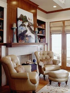 Off the foyer, a study exudes masculinity with stained paneling and built-in bookcases. Twin leather armchairs and an ottoman gather in front of a fireplace. Above, an artist's rendering of sand dunes adds one more view of the shore. (Photo: Photo: Jean Allsopp;)