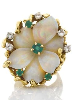 A carved opal, emerald, and diamond flower ring carved opal flower measuring approximately 26.1 x 19.5 x 7.7mm; signed Pac G.; mounted in eighteen karat gold.