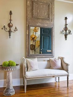 Ornate sconces and worn wood elements in this entryway scream classic country French style. The muted palette beautifully complements polished wood floors and crisp walls and trim. An oversize mirror bounces light around the space, while an upholstered bench provides a cozy spot to slip on shoes.