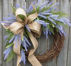 This lavender wreath is perfect to welcome spring and to use all summer long! Realistic lavender blooms are the main event in this wreath. A few pieces of realistic fern are used to compliment the lavender. A rustic wired burlap bow completes the look. This wreaths fern and blooms have a light and airy feel where the grapevine base is visible in places. Approximate Diameter (tip to tip): 20 This wreath was made on a grapevine wreath measuring approximately 17 Indoor/ Sheltered Outdoor s...