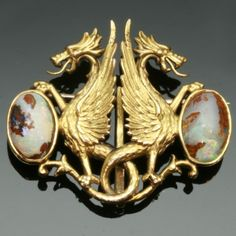 Charming Victorian brooch depicting two griffons protecting their egg.  Late Victorian / early Art Nouveau - The subject of this piece, although typical 19th Century, announces the coming of the Art Nouveau style.  Circa 1890, 14 karat yellow gold, cabochon opals