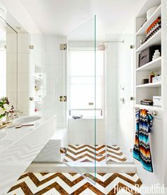 """In a New York City bathroom, designer Alla Akimova ran zig-zag tile straight into the shower stall. """"It makes the room feel larger,"""" she says. """"If I had changed materials, it would have interrupted the space."""" Custom cut floor tile by Manhattan Renovations. Yota shower system and Tara towel bar by Dornbracht.   - HouseBeautiful.com"""