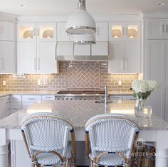 White and gray kitchen design with gray glass subway tile and white range hood. Design by Kim Wiederholt Design