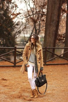 Winter outfit in Milan wearing camel coat and white denim pants. Also wearing striped sweater and wooden sunglasses.