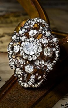 An antique silver-topped gold and diamond brooch. Featuring a centre old European-cut diamond, weighing approximately 1.65 carats, further enhanced by smaller old mine-cut diamonds, weighing a total of approximately 11.00 carats; measures 1-1/2 x 2 inches. #antique