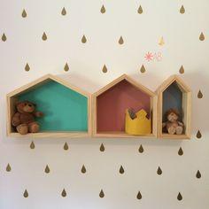 Adesivos de parede em forma de gotinhas douradas para encantar quartos infantis. Junto delas, nichos de madeira em forma de casinha, em 3 tamanhos e cores diferentes. - Ateliê Baobá