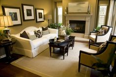 Greenish-brown walls wrap around this living room with fireplace, white sofa, two armchairs, dark wood coffee table, beige area rug with light green border placed on hard wood floor.