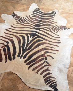 """""""Zebra Hide"""" Rug    Cowhide rug is stenciled with zebra stripes.  Each of our high-quality hairhide rugs is made from natural materials, and no two are alike. Unique variations in each hide add to the authentic look. Colors will vary; rug may not look exactly like the one shown.  6'6"""" x 7'6"""".  Size is approximate.  Imported."""
