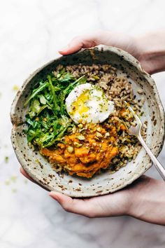 Bowl of sweet potatoes and brown rice with an egg and a fork.