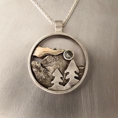Mountain Jewelry. This Mountain Pendant was hand fabricated using sterling silver and mokume gane. Atop the tree a bezel set blue Oregon Sunstone is set.