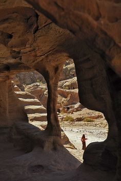 Cave With Roman Amphitheatre In The Background, Petra, Jordan _ Hidden amid the rock formations of Wadi Musa in Jordan, lies the ancient Nabataean city of Petra, Its facades were carved out of the red-hued rock more than 2,000 years ago.