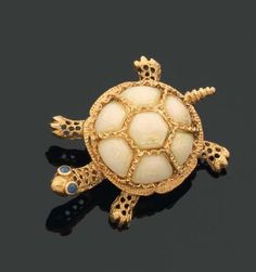 BROCHE en forme de tortue en or 18 kts émaillé blanc sur des fonds rayonnant.