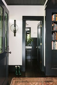Dark trim matches bookcases, white walls, wood ceiling matches trim, interior door could be an exterior door that shows off cool room through window. Dark Baseboards, Painting Baseboards, Painting Trim, Black Painting, Black Trim Interior, Black Window Trims, Dark Trim, House Trim, Black Doors
