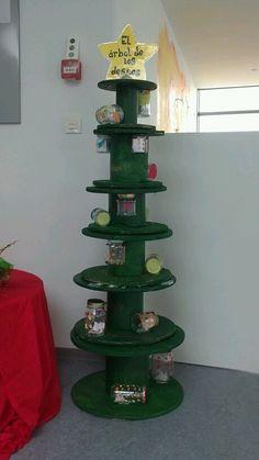 Árbol de Navidad con carretes de cable y botes de cristal pegados para poner los deseos.
