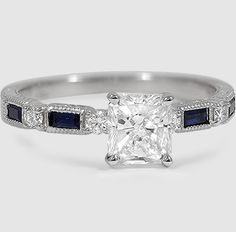 This vintage inspired ring features brilliant blue sapphire baguettes alternating with round diamonds and surrounded by delicate milgrain