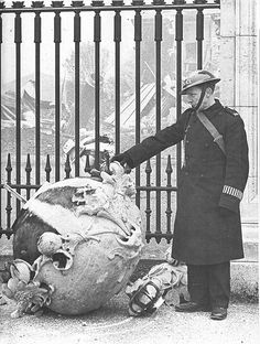 Buckingham Palace    On 8th March 1941 the north lodge of Buckingham Palace adjacent to Constitution Hill received a direct hit in a German bombing raid. Police Constable Stephen Robertson was killed by flying debris. The damage can be seen through the railings of Buckingham Palace, the war reserve Police Constable stands beside a piece of debris which has been thrown onto the pavement outside the Palace.