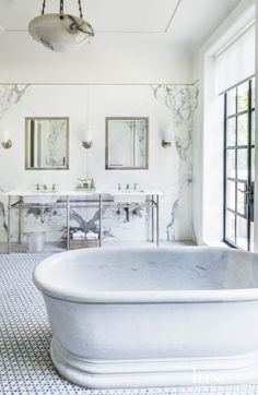 Eclectic White Bathroom with Marble Freestanding Tub. The beauty of the natural marble on the master bathroom walls is paired with a marble tub from Urban Archaeology and softened by the glow of brushed-nickel wall sconces by Waterworks. Luxe Interiors, Bathroom Renovation, Bathroom Inspiration, Bathroom Decor, Bathrooms Remodel, Beautiful Bathrooms, Beautiful Bathtubs, Free Standing Tub, Bathroom Design