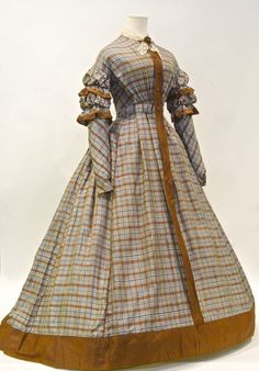 Dress: early 1860s. Silk with woven plaid pattern. Victoria wore tartan/plaid to honor Scottish. Still a lot of taffeta during this time.