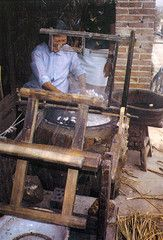 A Chinese woman at a silk farm, using the ancient technique for unwinding and reeling silk threads by immersing the cocoons in boiling water.