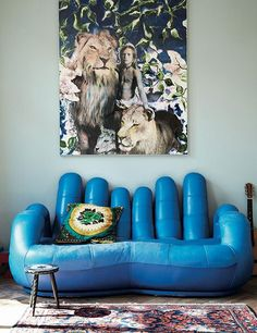 An electric-blue retro sofa pops against a teal wall.