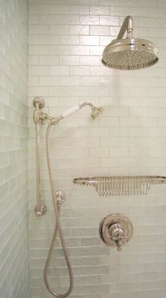 Exquisite master bath shower features iridescent glass tile shower surround as well as rain shower head, shower basket and vintage shower kit.