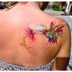 Messy watercolour tattoo of a hummingbird.
