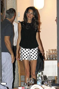 Amal Clooney steps out in Lake Como wearing polka dot shorts & a black top. See all her best looks here.