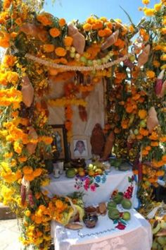This impressive ofrenda in Michoacan uses aromatic marigolds, colored corn, and very unusually shaped pan de muerto breads, that represent female spirits of the dead.