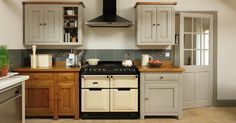 Create interest with a combination of painted finishes and natural materials with Freestanding Bastide Kitchen Furniture in Warm Oak and Oak Apple with Light Oak detail. Cream AGA Masterchef with Urban Slate Tiles and Lubelska Brick Floor Tiles.