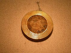 Amber disk with a gold rim, possibly worn as a pendant, from the Early Bronze Age burial of a woman, Preshute G1a. Popularly known as 'sun disks' these are frequently found as pairs and could have been worn as earrings but there is no certain evidence for this.